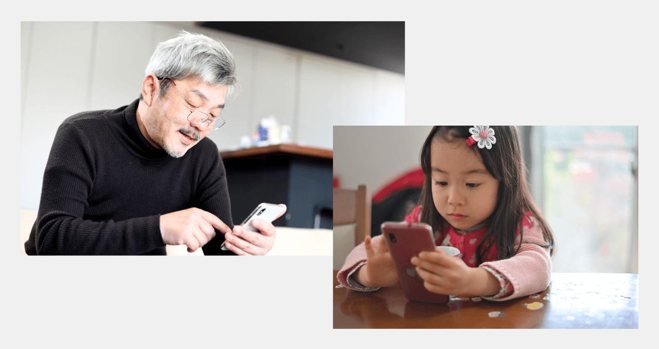 高齢者と子供がスマートフォンを操作しているイメージ写真